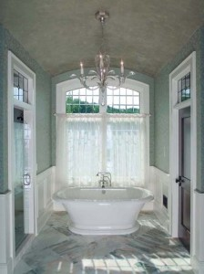 The luxurious bathroom is outfitted like other rooms, with furniture, a chandelier, and fine woodwork and glass.