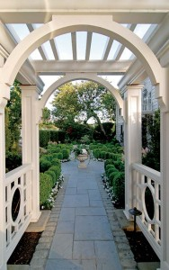 A pergola leading from the street frames the symmetrical lines of the yard.