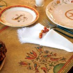 """The owners made the painted table cover in a design called """"Meadow""""; the dish pattern is """"Star Fraktur."""""""