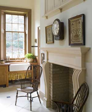 The painted wood fireplace was custom-made and lined in brick. The Belfast (or farmhouse) sinks rest on pine shelves, and the drainer and countertops nearby are also in wood. No window treatments have been used, as privacy is not an issue and the sash and trim are handsome.