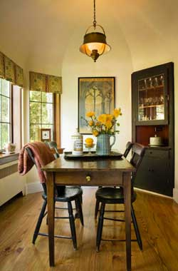 The Rutherfords spared the breakfast nook, refusing to sacrifice it for a larger kitchen. Two traditional china cabinets are painted black to set off the narrow French table.