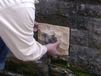 Fitting the new stone into the wall