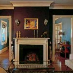 Eggplant walls in the living room are punctuated with new book-matched doorways, providing access to the dining room beyond.