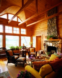 A fieldstone fireplace—which mimics the look of the rocky shoreline landscape—anchors the living space. A bank of casement windows opens to allow in salt air breezes. Walls are paneled in pine beadboard, while ceiling beams add interest to the space.
