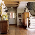 The main hall of the stone house offers exposed stone walls and salvaged hardwood floors.
