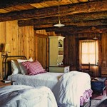 The guest room is truly rustic with its exposed log beams and vertical board walls.