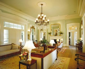 """Floor-to-ceiling windows were a common element in Greek Revivals, and in the living room they reach almost to the height of the 15-foot ceilings. """"A 6-foot 2-inch man can stand in the open window,"""" architect Jim Strickland says. The sashes are counterweighted, just as they would be in an old home, and disappear into a pocket in the ceiling when the windows are opened. The lighting fixtures are a mix of vintage and new pieces. Sidelights and transom lights set into ornate pediments around the door bring in light and allow views of the river and the wild southern landscape."""