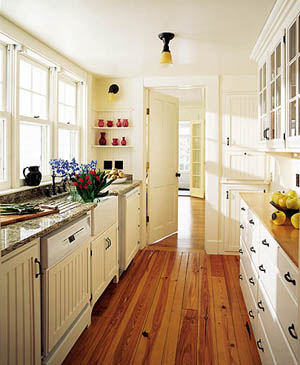 When Shepard is entertaining summer guests, the butler's pantry between the kitchen and dining room is the perfect spot to set up the bar. Its dishwasher and refrigerator are disguised behind bead board paneling. Vitzthum incorporated glass-paned cabinetry and Kohler's white farmhouse sink for a nineteenth-century look. The early twentieth-century reproduction lighting is by Rejuvenation. Wirsbo radiant flooring also warms the first floor, while reproduction radiators are found upstairs.