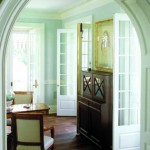 Historical trimwork surrounds an arched doorway that leads to the living room.