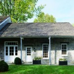 Tate added a flat-roofed structure with square columns across the side of the house to provide an open porch.