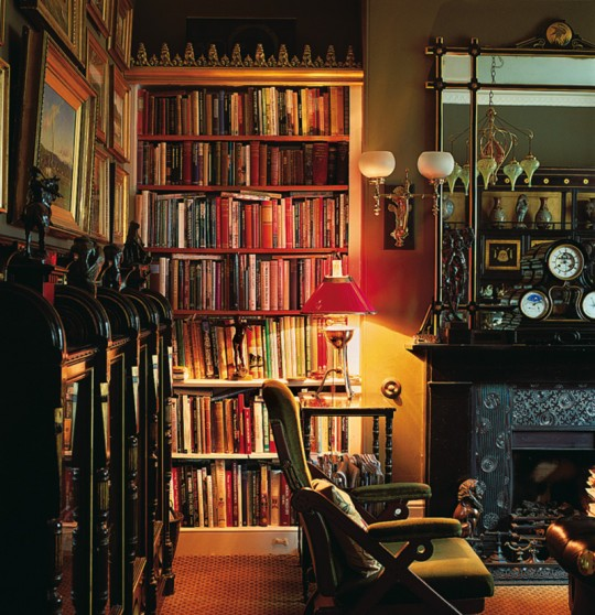 Books reside in bookcases (with Gothic cornice ornament) and in display cases in this home library in Great Britain.