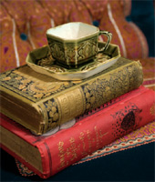 With their beautiful bindings, old books are themselves objets d'art. Two 19th-century volumes hold a ca. 1880 Linthorpe teacup on a button-tufted Aesthetic chaise.