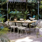Aluminum architectural panels define an intimate outdoor dining area where plant specimens thrive.