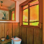 "On the window above the bidet, amber-tinted Kokomo seeded glass appears again, this time to add privacy and filter soft, diffused light into the space. ""When the sun comes through here in the morning, it just makes the perfect day,"" Jane says."