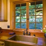 A copper sink with a built-in drainboard is the focal point of the galley-style kitchen.