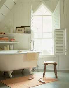 This Green cottage bathroom was enlarged, and simple new shelves were angled next to the restored clawfoot tub.