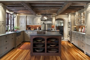 The kitchen floor was created from century-old wood repurposed from another (dilapidated) Will Price-designed house; many countertop appliances are hidden behind the custom cabinets. Two beams added across the ceiling bolster the home's structural support, and are made of steel and salvaged barn beams sistered together with matching bolts.
