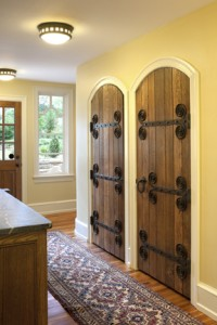 Twin radius-topped doors featuring elaborate strapwork hinges signed by Samuel Yellin were moved from the dining room to the mudroom, where they would be more visible.