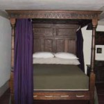 The handsome bed is a replica with bed-hangings by the owner and a linsey-woolsey coverlet from The Seraph.