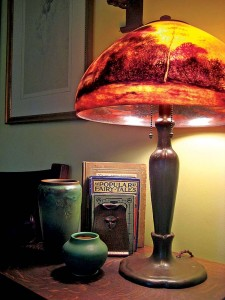 Reverse-painted shades featuring natural scenes were a specialty on Handel's Arts & Crafts lamps (shown here in the company of a Rookwood carved Green Vellum vase and a pair of Roycroft trillium bookends).