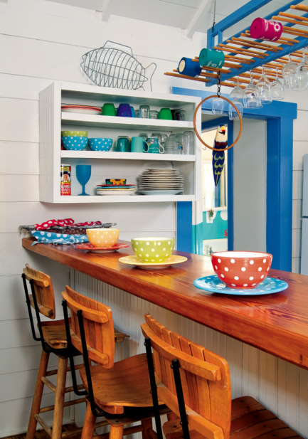 A tiny, plank-walled cottage kitchen makes the most of open shelving and an overhead rack for stemware.