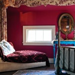 A full set of toile drapery, hung from the sloped ceiling upstairs, inspired the fuchsia–red paint. The brass bed is a very old family piece.