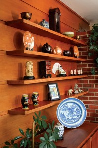 The horizontal, inverted board-and-batten paneling and cantilevered shelves are classic Usonian elements, as is the display of Asian pieces.