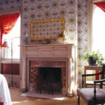 The formal parlor has geometric wallpaper, from Brunschwig, and simple red swags ast the windows.