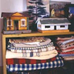 Collected vintage textiles and toy houses occupy shelves in one bedroom under the eaves.