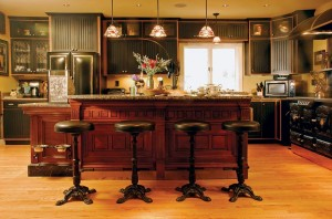 Cast-iron barstools salvaged from a local restaurant belly up to the printer's desk-turned-island in Bruce and Melanie Rosenbaum's Victorian kitchen.