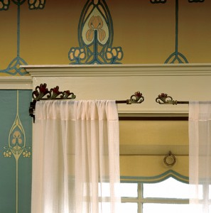 C.J. Hurley created a contrasting scheme with a Swedish blue-green paper accented with pink irises and yellow cartouches against a handpainted frieze above. The neutral ivory trim creates harmony. Note the subtle coordination of the window shade with the color scheme.