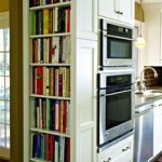A tall shelf built into kitchen cabinets puts cookbooks within easy reach, and their colorful spines help brighten up the all-white decor. [Photo: Plain & Fancy]
