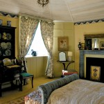 """The Georgian Bedroom was enhanced with a faux-painted """"tented"""" ceiling painted by Bob Parsons; curtain fabric is from Laura Ashley."""