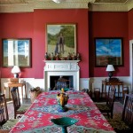 The dining room features a 19th-century kilim on the table, and the ceiling is still covered with an 1898 Morris paper;a portrait by Rob Collins of Bob Parsons with his Great Dane hangs over the mantel.