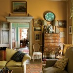 The drawing room was painted in warm terracotta and furnished with comfortable seating and antiques of the period.Note the handsome door entablature. The back hall and kitchen are beyond.