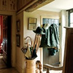 Coats, umbrellas, and boots, essential gardening accoutrements, hang in the east entry hall opening to the walled garden.