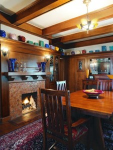 An Arts & Crafts aesthetic is strong in the dining room, with its original oak woodwork. The sturdy massing of high wainscot, beams, and corbelled mantelshelf are tempered by colorful Hill pottery, along with later art glass and Art Deco lighting—a rich interior free from rectilinear gloom. Unique, antique geometric tiles surround the gas fireplace.