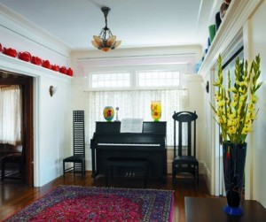 The entry hall suggests London more than the Bay Area. Black Mackintosh-designed chairs are graphic statements against the long-ago-painted trim. Collected Hall pottery  on the plate rail creates a frieze. Art Deco fixtures are used throughout.