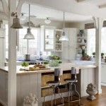 The kitchen is open and airy, with white cabinetry and wood floors.