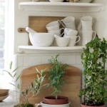 Pewter pots, antique cutting boards, and ironstone line the kitchen shelves.
