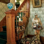 Bradbury's Dresser-designed 'Lily' in Jasper Green papers the entry and stairwell. The mysterious Turkish maiden is a calling-card receiver. A rare blown-glass newel lamp, ca. 1880, is a colorful accent.