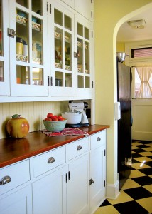 The butler's pantry, outfitted with original hardware, a new wood countertop, and retro Royledge shelf edging, houses vintage dishware and kitchen accessories, like a 1950s-era Sunbeam mixer.