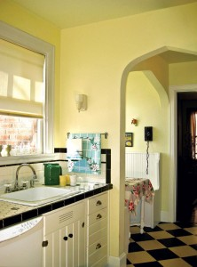 The shallow single-bowl sink and faucet with porcelain cross handles were must-haves for the couple's retro kitchen.