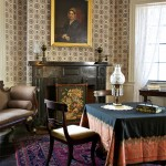 In the family parlor, Empire and Victorian furnishings coexist with the Federal-era wallpaper, reproduced by Adelphi from a Plymouth-area document in the archive of Historic New England. The portrait is of Eunice Denny Burr Hedge.