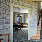 The best parlor and the entry hall have documented wallpapers reproduced by Adelphi Paper Hangings; carpets were selected from an appropriate design archive and woven through J.R. Burrows & Co. Furnishings cover the range of the family's occupancy; the Victorian gasolier is an original.