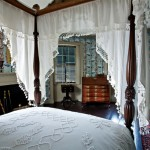 Antique dimity bed-hangings have been restored to the four-poster bed, a family piece still in the house.