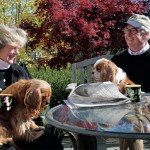 """Beverly and John Sullivan have coffee and the morning paper outside, here with two of their four """"kids."""""""