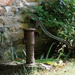 The old pump, a local farm piece, is rustic against the stonework of the icehouse.