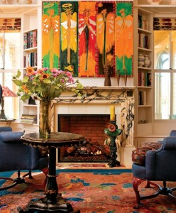 """Lined with shelves and window seats, the den overlooking the pond is more descriptively called the Winter Room. Its mantel (resized for code-compliance with the gas fireplace) came from the Plaza Hotel in New York City. The painting is """"Angels with Mirrors,"""" purchased at the Fearington (N.C.) Folk Art Festival."""