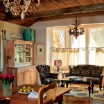 The dine-in kitchen has a sitting area in the bay window. The cabinet came from Antiques & Interiors in High Point, N.C. The mantelpiece actually hides a television and storage. Chandeliers and the mudroom door are salvage. The sofa is upholstered in Uzbek suzanis from ABC Carpet & Home.